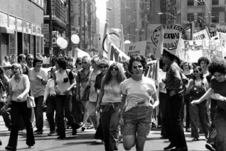 """Celebrating the second annual Christopher Street Gay Liberation Day, marchers cross 34th Street in New York, June 27, 1971. The march, moving from Greenwich Village up Sixth Avenue, will end with a rally in Central Park. More than 3,000 people participate in the parade marking the end of """"Gay Pride Week' in New York City."""