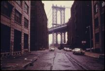 MANHATTAN_BRIDGE_TOWER_IN_BROOKLYN,_NEW_YORK_CITY,_FRAMED_THROUGH_NEARBY_BUILDINGS._BROOKLYN_REMAINS_ONE_OF_AMERICA'S..._-_NARA_-_555898