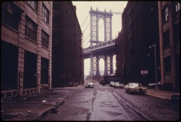 MANHATTAN_BRIDGE_TOWER_IN_BROOKLYN,_NEW_YORK_CITY,_FRAMED_THROUGH_NEARBY_BUILDINGS._BROOKLYN_REMAINS_ONE_OF_AMERICA'S..._-_NARA_-_555898